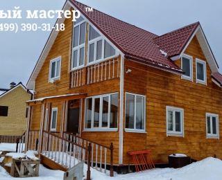Обшитый имитацией бруса деревянный каркасный дом