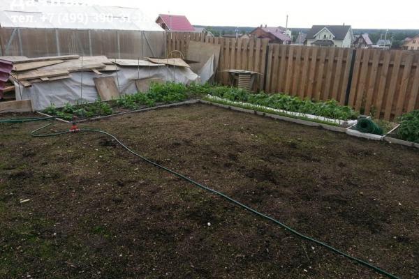 Готовые грядки с насаждениями и площадка с газонной травой перед поливом