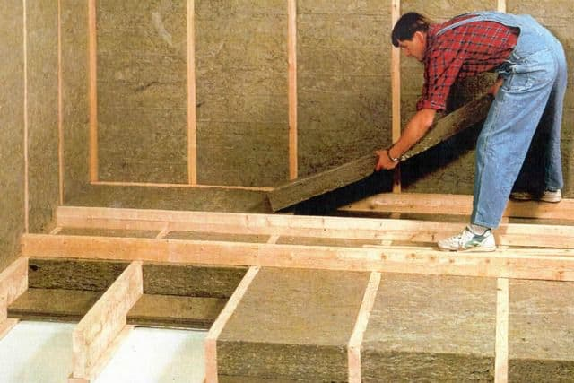 The insulation of a frame house, using boards or mats